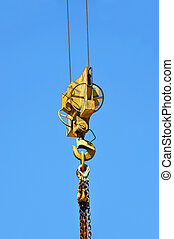 Crane winch with hook on blue sky background