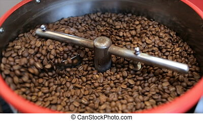 Mixing roasted coffee. Close up