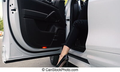 Women's heels come out of an expensive car. Woman legs in...