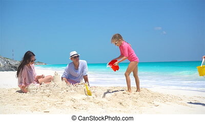 Family with two kids making sand castle at tropical beach -...