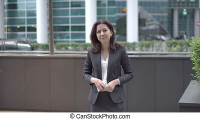 Woman in business clothes approaching to the camera