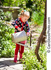 The little girl waters a kitchen garden