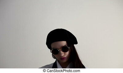 A Young woman in shirt, sunglasses and beret, on the white...