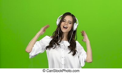 Brunette with headphones in her ears is having fun. Green...