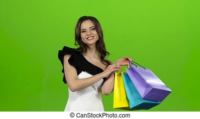 Brunette went shopping, she bought a lot of things. Green...