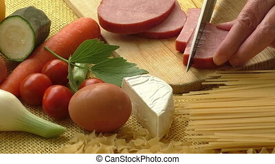 Pork ham on a wooden cutting board with fresh vegetables