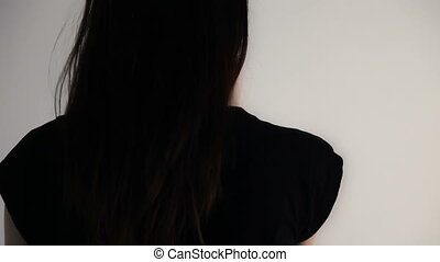 Young woman touches her hair and looks over her shoulder