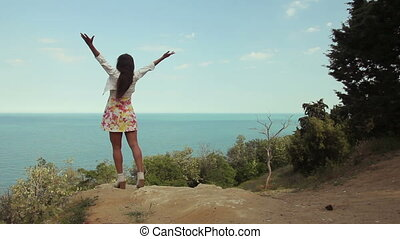 Young woman raising hands to the ocean