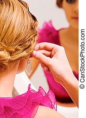 Trying on earrings - Image of pretty female putting on...