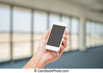 Hand holding blank screen mobile phone with abstract blurred...