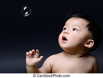 little asian baby boy looking soap bubble.
