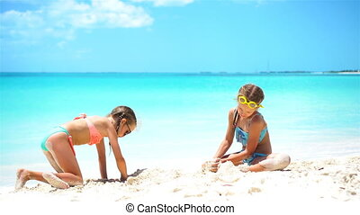 Happy little girls playing with beach toys during tropical...