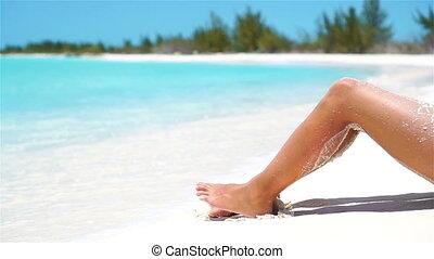 Female slim tanned legs on a white tropical beach. - Female...
