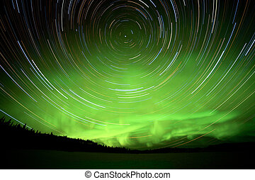 Star trails and Northern lights in night sky -...