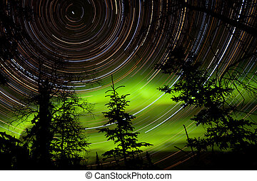 Star trails and Northern lights in sky over taiga -...