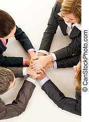 Teamwork - Image of business people keeping hands on top of...
