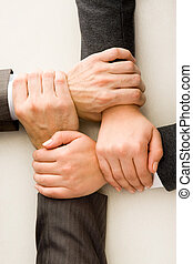Partnership - Image of crossed hands over workplace