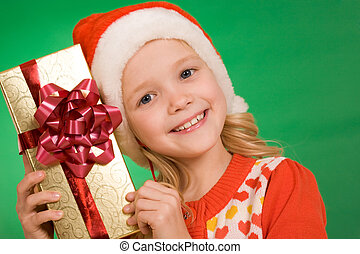 Christmas surprise - Cheerful girl in Santa cap holding...