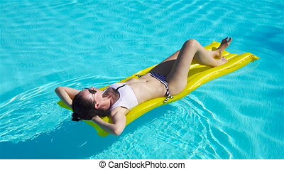 Woman relaxing on inflatable air mattress at turquoise water...