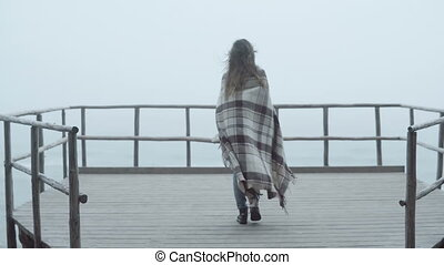 Back view of young woman with plaid standing on the wooden...
