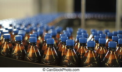Plastic bottles of beer on a conveyor belt factory -...