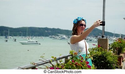 Young pretty woman with flower in her hair taking selfie picture on vacation. 3840x2160