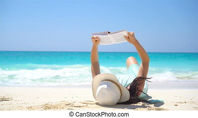 Young woman is reading on tropical white beach - Young woman...