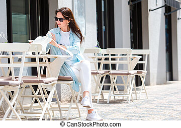 Young woman sitting in a cafe outdoor drinking coffee. Happy...