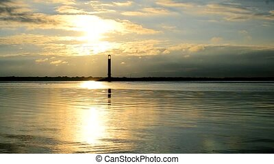 Water landscape at dawn in the morning with lighthouse on...