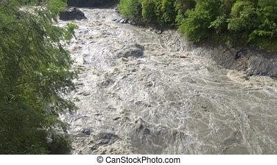 Flood water fast flowing down swollen mountain river in...