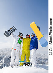 Winners - Portrait of three successful snowboarders raising...