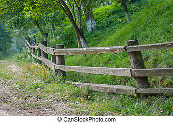 old sparse fence of unpainted laths against the background of green plants