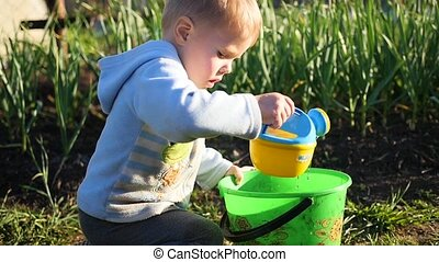 A child with a small watering can water the grass in the...