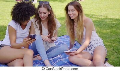 Smiling women with smartphones talking - Group of cheerful...