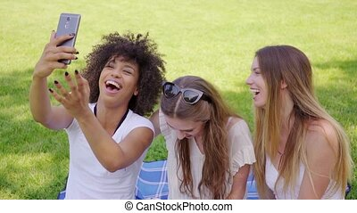Happy women taking selfie in park - Three pretty young girls...