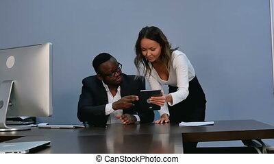 Two young business partners using touchpad at meeting. Slow...