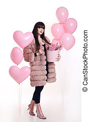 Fashion photo of fashionable woman in pink fur coat with rose bouquet of flowers in hat box over balloons isolated on white studio background.