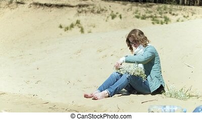 Woman staying on a beach with flower at the sunny day