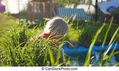 girl playing in the Park near a pond. Summer Sunny day