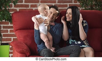 Happy parents play with a little blond boy.