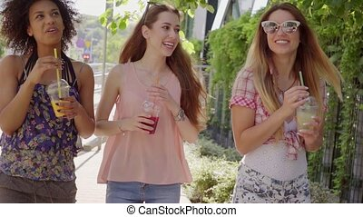 Women walking and having beverages - Happy young black and...