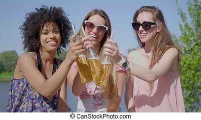 Young women clinking beer - Three young black and white...