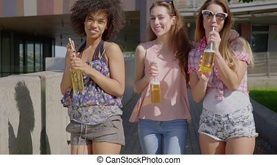Women walking and having beer - Three young multiracial...