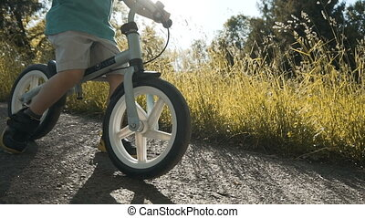 Kid Riding Bicycle - Little boy riding the bicycle against...