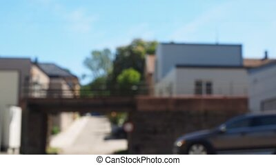 Car and people passing under a rocky train bridge