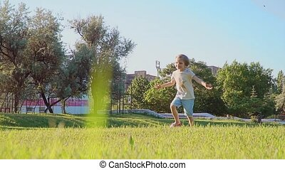 Daughter rushes into mother's arms and gives her a big hug. Outside in the park. Sunset. Slow motion.