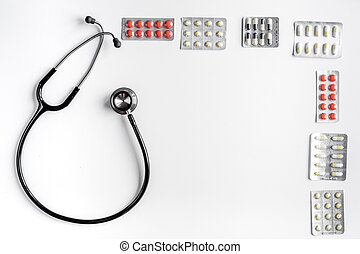 Medical equipment with stethoscope and pills in doctor's office on white desk background top view mock-up
