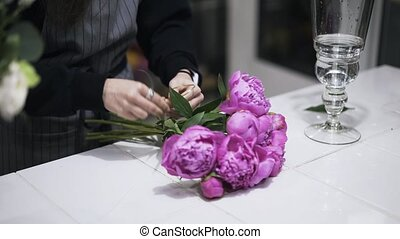 Close up of flower shop assistant tieing bunch of pink flowers