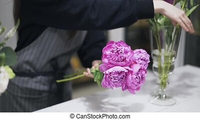 Close up of woman florist making a bunch of pink flowers