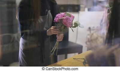 Woman florist making a bunch of pink flowers and branches